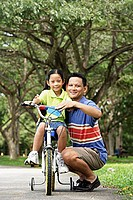 Girl on bicycle, father crouching down next to her, both looking at camera