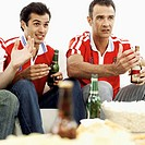 Close-up of two young men watching television wearing soccer jerseys
