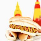 Close-up of a pile of hotdogs served with mustard