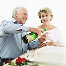Elderly man pouring champagne into a woman´s glass