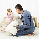 Father and daughter (5-6) having a pillow fight