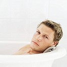 Young man lying in a bathtub