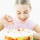 Close-up of a teenage girl (16-18) inserting a spoon into a bowl of fruit trifle