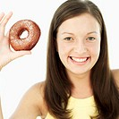 Young woman holding up a doughnut