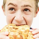 Close-up of a teenage boy (15-17) eating a croissant (blurred)