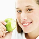 Close-up of a teenage girl (15-17) holding a green apple