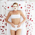 Young woman lying on bed in underwear with face pack and rose petals strewed about