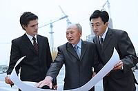 Businessmen looking at blue print, cranes in the background