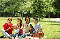 Young adults having picnic in park, looking at camera