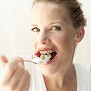 Close-up of a young woman eating a spoonful of cereal