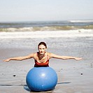 Portrait of a young woman exercising with an exercise ball