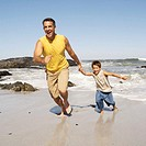 Father and son holding hands running on the beach