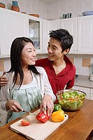 Couple in kitchen, smiling at each other, woman cutting vegetables