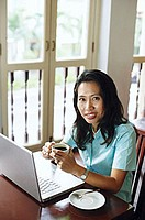 Woman using laptop, holding cup, looking at camera