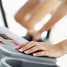 Close-up of young woman´s hand pressing treadmill button
