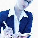 Close-up of a woman writing with a pen on a notepad