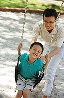 Father and son in playground, father pushing son on swing