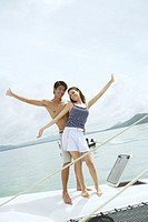 Couple on boat, looking at camera, arms outstretched