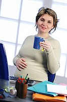 PREGNANT WOMAN WITH A DRINK<BR>Model.<BR>Woman five months pregnant.