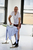 Man in underwear ironing his clothes.