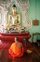 Buddhist monk meditates in front of Buddha statue, Yangon, Burma