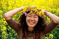 Young beautiful chinese women wearing a rape flower crown. Luoping, Yunnan province. China