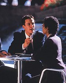 close-up of a man discussing business with a woman at an outdoor cafe