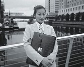 portrait of a businesswoman standing against a railing and holding a briefcase (black and white)