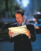 portrait of a businessman standing outdoors holding a newspaper