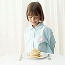 Young girl (8-9) looking at plate of pancakes and syrup