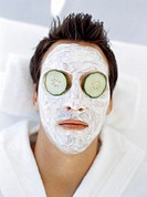 close-up of a young man wearing a facial mask with cucumber slices on his eyes