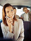 businesswoman talking on a mobile phone with two businessmen sitting behind her