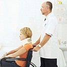 Side profile of an elderly male doctor pushing a young woman in a wheelchair