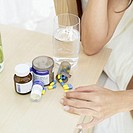 Elevated view of a woman´s hand resting on a locker with pills and a glass of water beside it