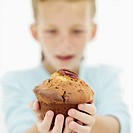 Close-up of a boys hand holding out a muffin (blurred)