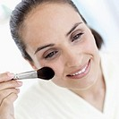 Close-up of a woman applying makeup with brush