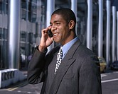 Side profile of a young businessman talking on a mobile phone outdoors