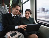 Young businessman and a young businesswoman sitting together on a train working on a laptop