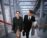 Elevated view of a young businesswoman and a young businessman walking up steps