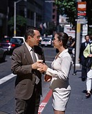 Young businessman and a young businesswoman standing on the sidewalk talking to each other