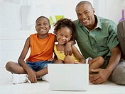 portrait of a father and his children in front of a laptop