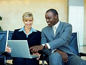 businessman and a businesswoman pointing towards a laptop