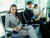 portrait of a businesswoman sitting on a bench holding a mobile phone at an airport