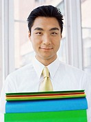 portrait of a businessman holding a stack of files