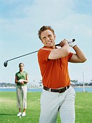 young man swinging a golf club