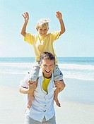 portrait of a father carrying his son on his shoulders at the beach