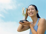 low angle view of a female athlete holding a trophy