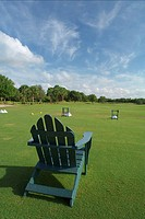 Empty adirondack chair on a golf course