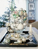 Close-up of Christmas ornaments with a candlestick holder and plates on a tray