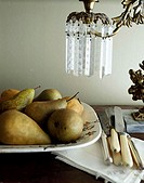 Close-up of pears with knives on a table